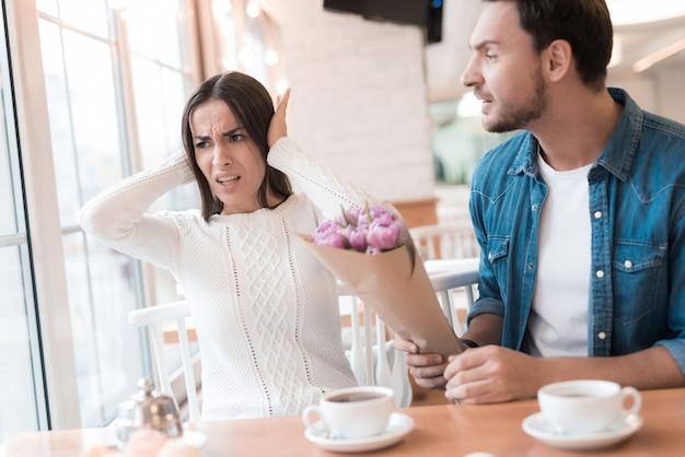 Beleidigter mädchen-mann mit blumen-streit im café.