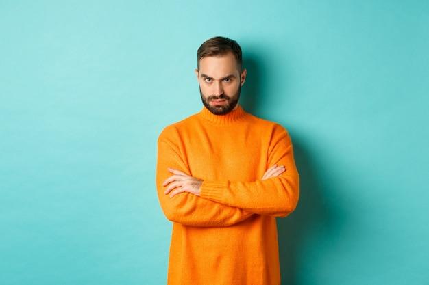 Beleidigter mann, der dich wütend ansieht, die arme auf der brust verschränkt und wütend starrt und in einem orangefarbenen pullover gegen die türkisfarbene wand steht.