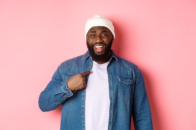 Beleidigter und verwirrter afroamerikanischer mann, der auf sich selbst zeigt, belästigt in die kamera starrt, beschuldigt wird und über rosafarbenem hintergrund steht.