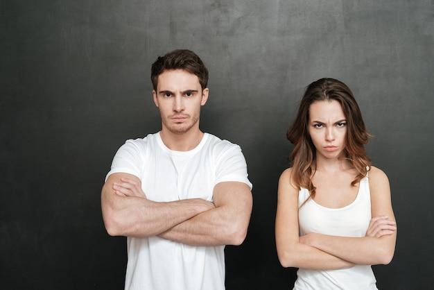 Beleidigtes junges paar, das mit verschränkten armen steht. isolierte dunkle wand