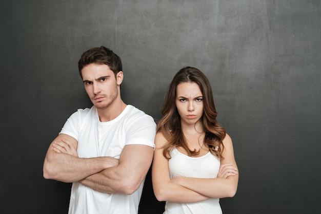 Beleidigtes paar, das mit verschränkten armen steht. isolierte dunkle wand