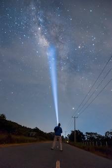 Beleuchten sie die milchstraße auf der dorfstraße mit einer taschenlampe im drak