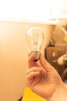 Beleuchtete glühbirne in der hand der frau, fotokreativ- und freiberuflerarbeitsplatz im hintergrund