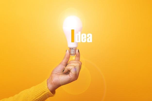 Beleuchtete glühbirne mit inschrift idee über gelbem hintergrund
