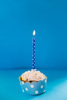 Beleuchtete kerze über dem dekorativen kleinen kuchen auf blauem hintergrund