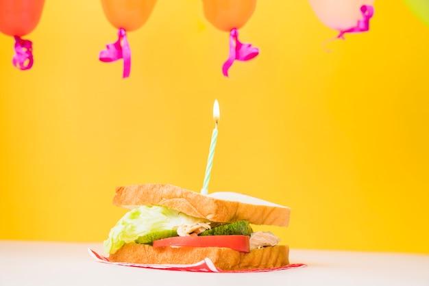 Beleuchtete kerze über dem sandwich gegen gelben hintergrund