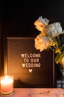 Beleuchtete kerze und rosen in der nähe des schwarzen rahmens mit willkommen zu unserer hochzeitsbotschaft