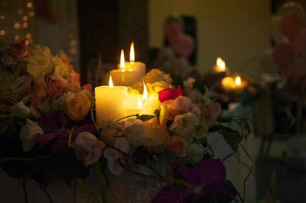 Beleuchtete kerzen auf einem hochzeitstisch braut und bräutigam in einem restaurant.
