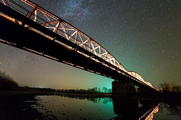 Beleuchtete metallbrücke auf betonstützen, die im wasser am dunklen sternenhimmel mit milchstraßenkonstellation reflektiert werden. nachtfotografie-konzept.