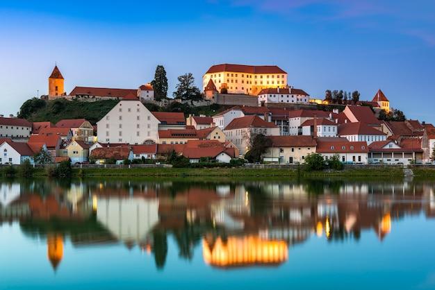 Beleuchtete stadt ptuj in slowenien in der dämmerung