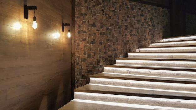 Beleuchtete treppe mit holzstufen und nachts beleuchtet im inneren eines großen hauses