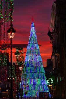 Beleuchteter weihnachtsbaum, der in der dämmerung in der mitte des platzes puerta del sol in madrid steigt.