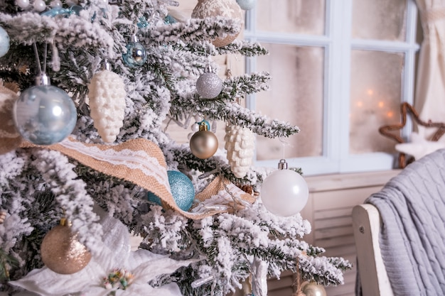 Beleuchteter weihnachtsbaum, geschenke, kamin, strümpfe. weihnachten und neujahr, wohnkultur. weihnachtsbaum in der nähe von kamin. interieur, magische atmosphäre. kerzen und geschenkkartons