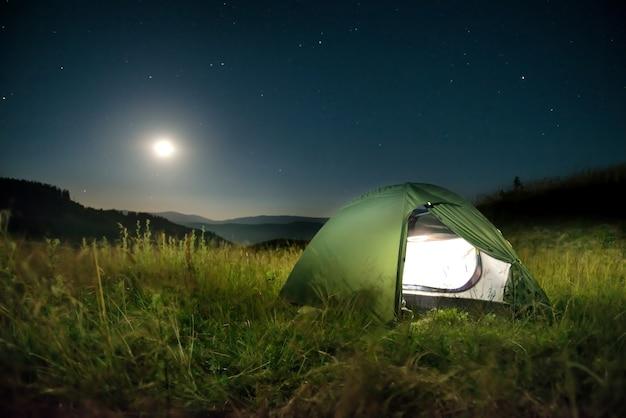 Beleuchtetes grünes zelt in den bergen nachts unter dunklem himmel mit vielen sternen