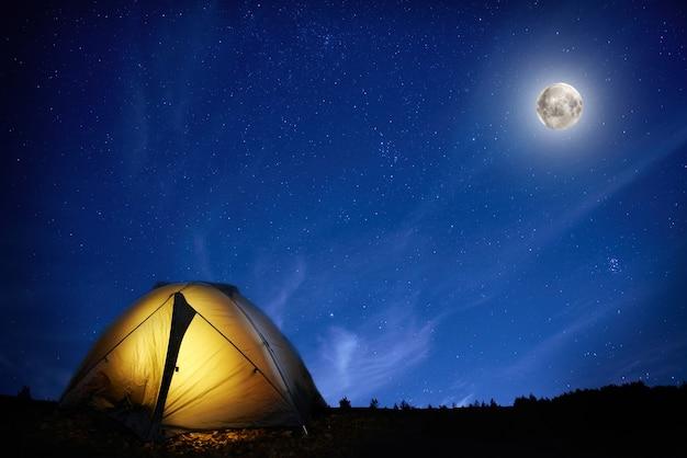 Beleuchtetes orangefarbenes campingzelt unter mond und sternen in der nacht