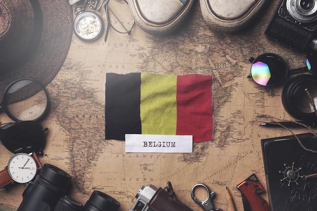 Belgien-flagge zwischen dem zubehör des reisenden auf alter weinlese-karte. obenliegender schuss