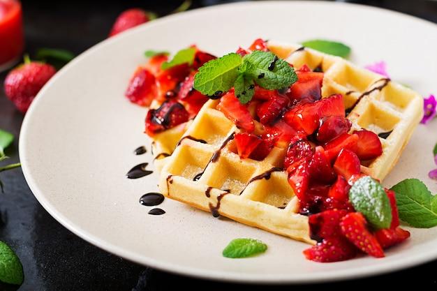 Belgien-oblaten mit erdbeeren, schokolade und sirup auf einer platte.