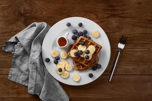 Belgische haferflocken-waffeln mit banane und blaubeere auf rustikalem holztisch