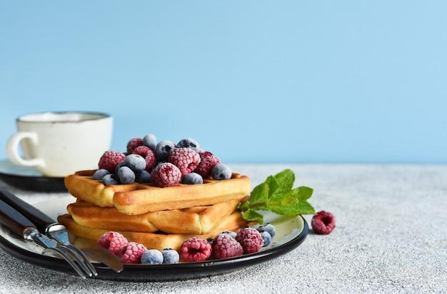 Belgische vanillewaffeln mit beeren und einer tasse kaffee zum frühstück.
