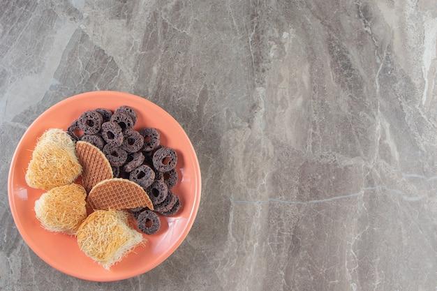 Belgische waffel, kadayif und maisringe auf platte auf marmor.
