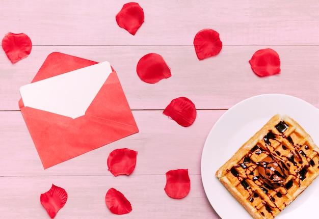 Belgische waffel mit blumenblättern und umschlag der roten rosen