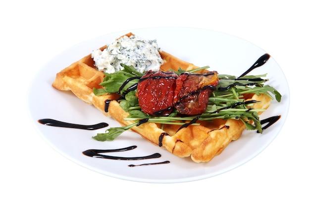 Belgische waffel mit frischkäse und gebackenen paprika, liegt auf platte, isoliertes bild auf weißem hintergrund.