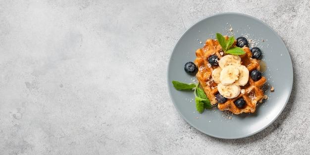 Belgische waffel mit honig, banane, nüssen und blaubeeren