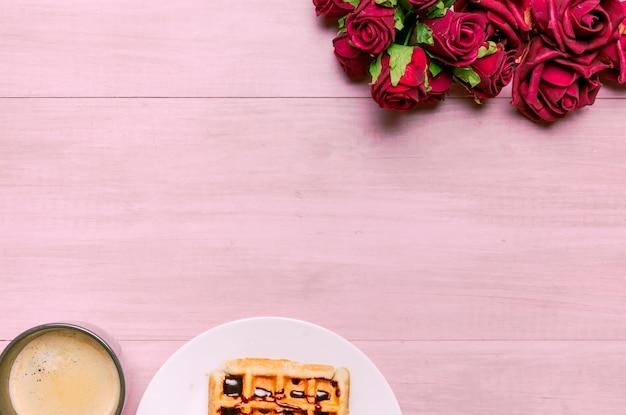 Belgische waffel mit rosenblumenstrauß und -kaffee