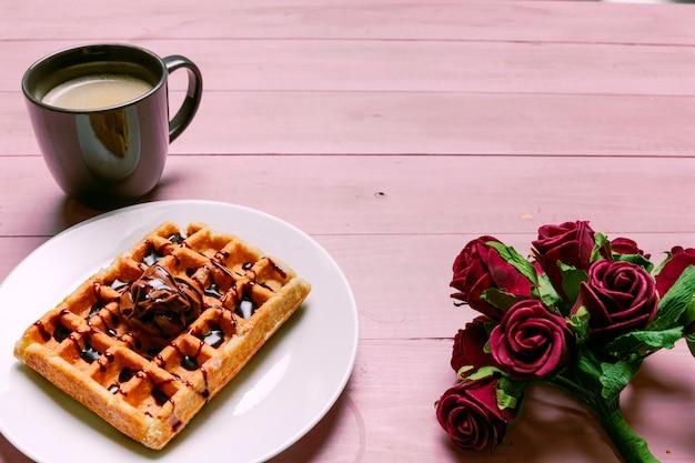 Belgische waffel mit rosenblumenstrauß und kaffeetasse