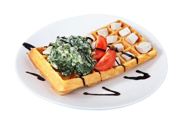 Belgische waffel mit salat, gewürfeltem käse und tomatenscheiben, liegt auf platte, isoliertes bild auf weißem hintergrund.