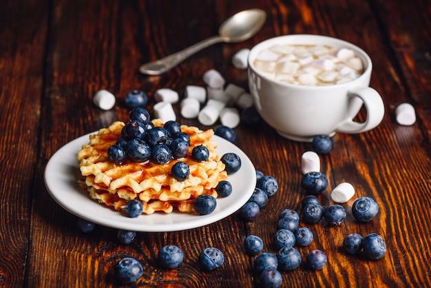 Belgische waffeln auf teller mit frischer blaubeere und tasse heißer schokolade mit marshmallow