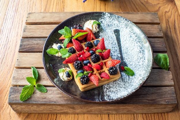 Belgische waffeln mit erdbeeren, blaubeeren, brombeeren und sirup