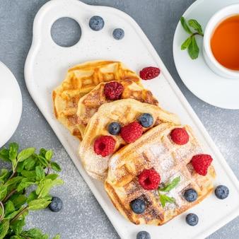 Belgische waffeln mit himbeeren, blaubeeren, tee, draufsicht. gesundes hausgemachtes frühstück