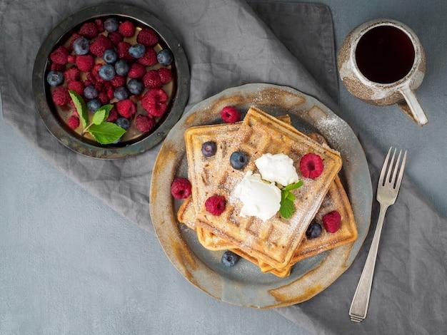 Belgische waffeln mit himbeeren, schokoladensirup. frühstücken sie mit tee auf dunklem hintergrund, draufsicht