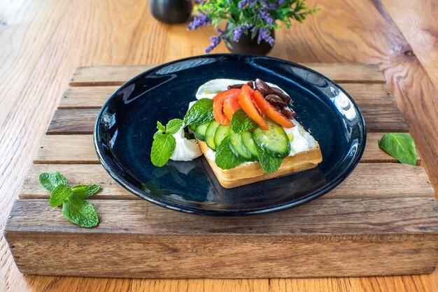 Belgische waffeln mit käse, oliven, tomaten und minze auf einem holztablett