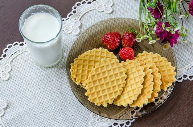 Belgische waffeln mit milch und erdbeeren auf weißer tischdecke