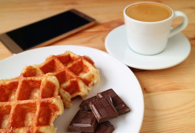 Belgische waffeln und dunkle schokoladenstücke mit verschwommenem heißem kaffee und smartphone im hintergrund