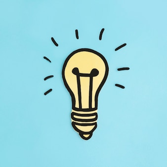 Belichtete gelbe glühlampe des papierausschnitts auf blauem hintergrund