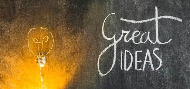 Belichtete glühlampe mit dem großen ideentext geschrieben auf tafel