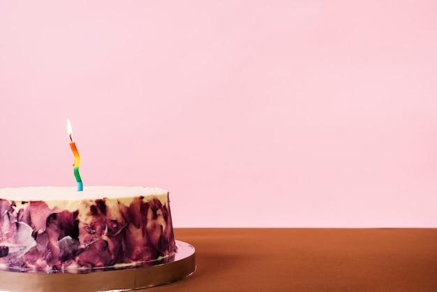 Belichtete kerze auf köstlichem kuchen gegen rosa hintergrund