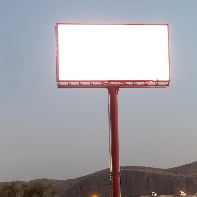 Belichtete unbelegte anschlagtafel für reklameanzeige gegen blauen himmel