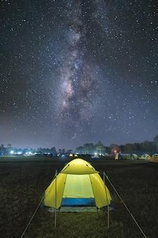 Belichtetes touristisches zelt unter schönem nächtlichem himmel voller sterne und milchstraße