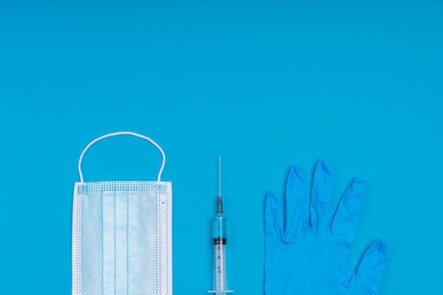 Beliebte medizinische antivirale maske, eine spritze mit einem virusimpfstoff und medizinischen handschuhen auf einer blauen oberfläche