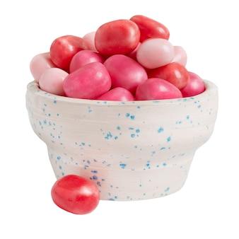 Beliebter runder kaugummi in einer schüssel auf weißem hintergrund. leckere süßigkeiten für den urlaub.