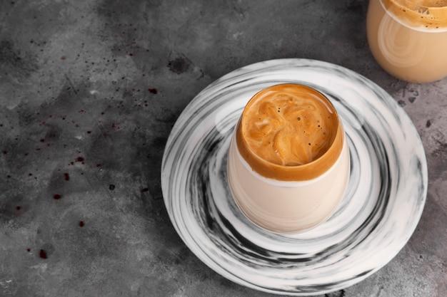 Beliebtes getränk koreanischer dargon-kaffee aus instantkaffee, zucker, heißem wasser und milch im glas auf grauem hintergrund. speicherplatz kopieren