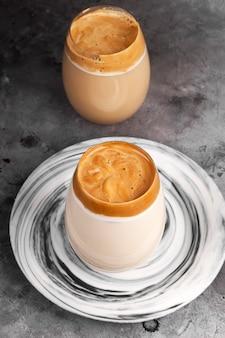 Beliebtes getränk koreanischer dargon-kaffee aus instantkaffee, zucker, heißem wasser und milch im glas auf grauem hintergrund