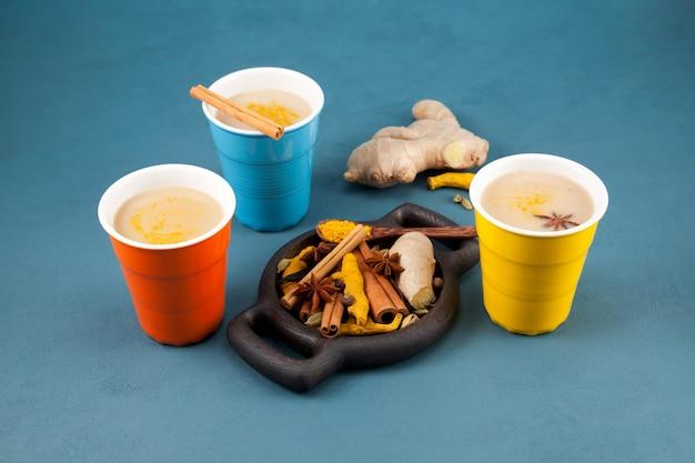 Beliebtes indisches getränk in bunten keramikgläsern neben den zutaten.