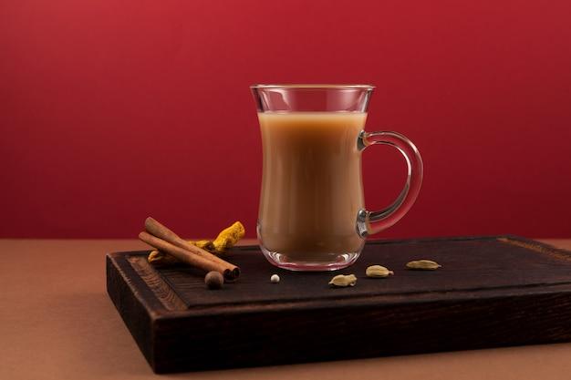 Beliebtes indisches getränk karak tee oder masala chai. zubereitet mit der zugabe von milch, verschiedenen gewürzen und gewürzen.