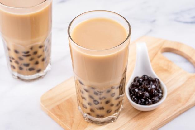 Beliebtes taiwan-getränk - bubble-milchtee mit tapioka-perlenkugel im trinkglas auf holztablett des weißen marmortisches