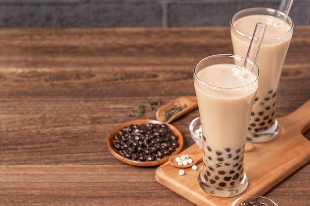Beliebtes taiwan-getränk bubble-milchtee mit tapioka-perlenkugel im trinkglas und im strohholztisch